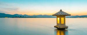Ruhiges kleines Häuschen auf stillem See in Abenddämmerung mit warmem Licht