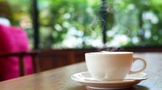 Weiße Tasse mit Dampf auf Tisch vor grünem unscharfem Wald