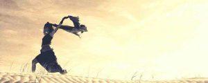 Shilouette eine rennenden Frau auf einer Duene mit erhobenen Händen und wehendem Schal