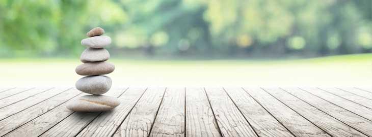 gestapelte Zen-Steine auf Holzbrettern vor grünen unscharfen Bäumen