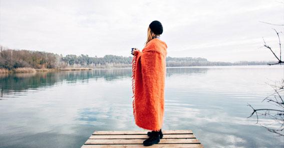 Frau mit orangefarbener Decke und Tasse in der Hand steht auf einem Steg und schaut auf eine hellgraue See-Landschaft
