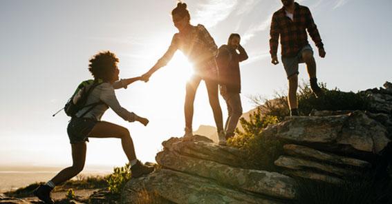 Vier Wanderer helfen sich im Gegenlicht beim Klettern auf einen Felsen in einer weiten Ebene