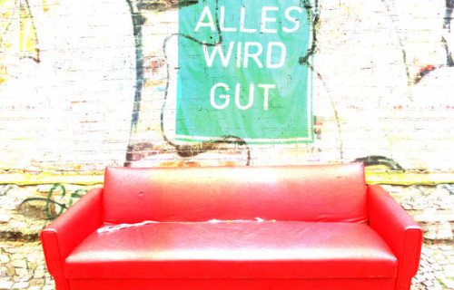 Rotes Ledersofa auf hellen Gehwegsteinen vor weißer Mauer mit günder Fahne, auf er in weißer Schrift steht: Alles wird gut.
